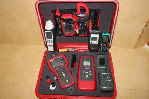 Красный чемоданчик электрика с контрольно измерительным инструментом.